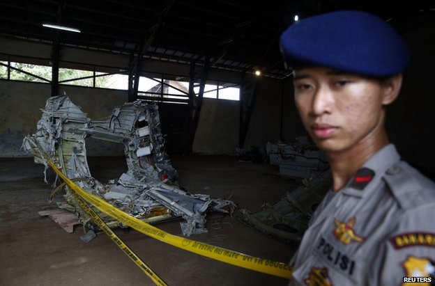 A policeman guards fuselage debris inside a storage facility at Kumai port in Pangkalan Bun, 19 January