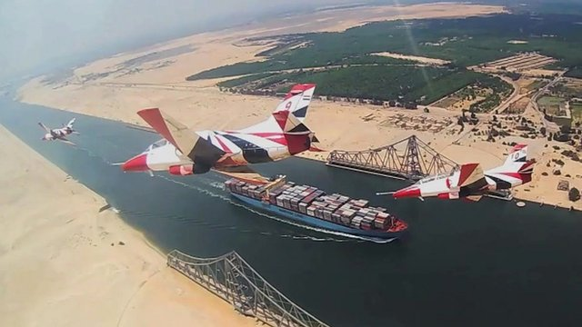Planes fly over ship on Suez Canal