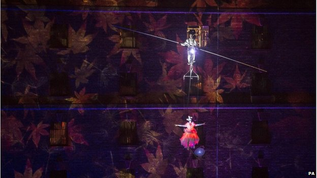 Circus artists cycle on a high-wire