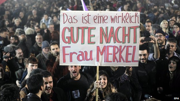 """A poster held by Syriza supporters reads, """"This is a really good night, Mrs Merkel"""""""