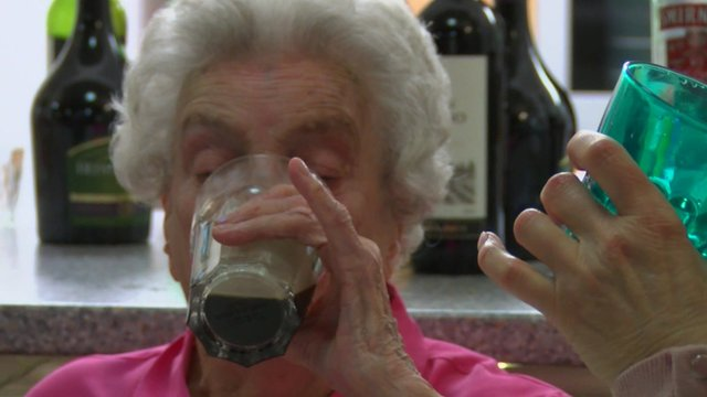 Elderly woman drinks cocktail