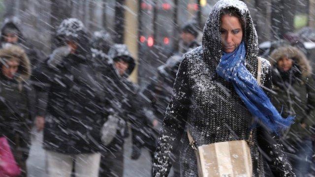 Pedestrians make their way through driving snow in midtown Manhattan in New York, Monday, Jan. 26, 2015