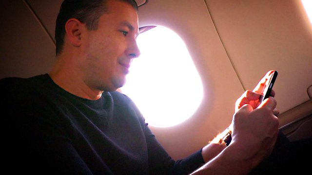 A man using a smartphone on a plane