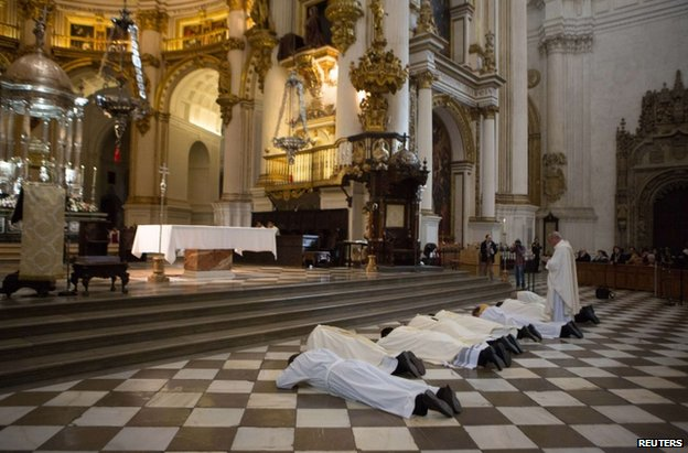 The Archbishop of Granada, Francisco Javier Martinez, and fellow priests prostrate themselves in front of the altar of Granada's cathedral