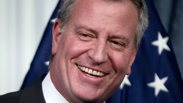 New York City Mayor Bill de Blasio smiles during a news conference to announce a tentative contract agreement with the Uniformed Superior Officers Coalition at City Hall in New York, 9 December, 2014