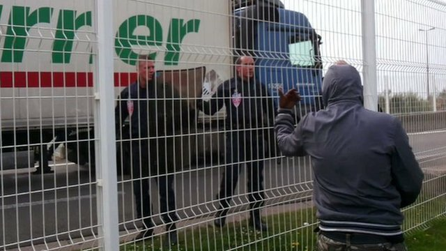 A migrant gestures at police