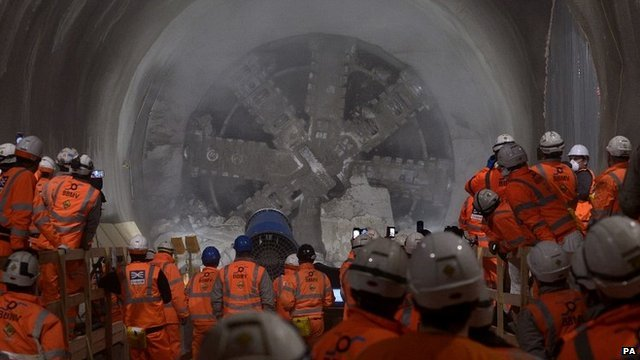 """Workmen look on as tunnel machine, named Elizabeth after the Queen, to break through into the east end of Crossrail""""s Liverpool Street station in London"""