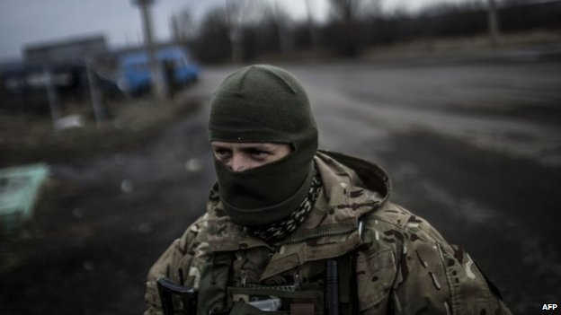 A Ukrainian soldier stands watch on a road between Debaltseve and the Ukrainian-controlled town of Artemivsk in the Donetsk region - 2 February 2015