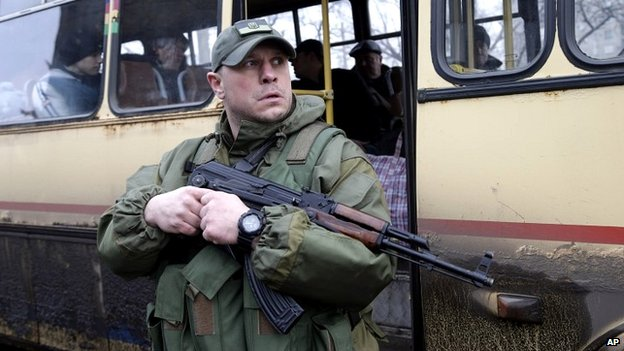 A Ukrainian soldier holds a weapon as people wait on a bus to leave the town of Debaltseve in Artemivsk, Ukraine - 3 February 2015