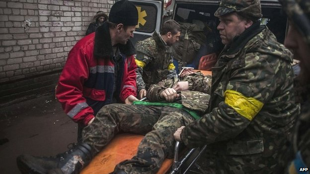 Ukrainian troops help a wounded soldier after clashes with pro-Russian rebels near Debaltseve in the Donetsk region - 2 February 2015
