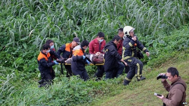 """Rescue personnel carry a passenger from a TransAsia ATR 72-600 turboprop plane that crash-landed into a river outside Taiwan""""s capital Taipei on a stretcher in New Taipei City on February 4, 2015"""