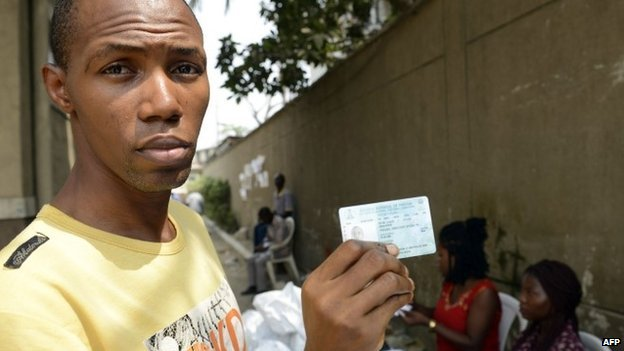 A voter shows his Permanent Voter's Card (PVC) after receiving it from officials of the Independent Electoral Commission in Lagos on 24 January  2015