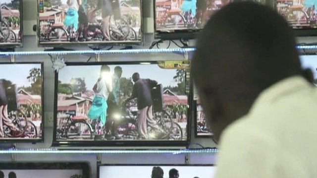 A man watches several TV screens