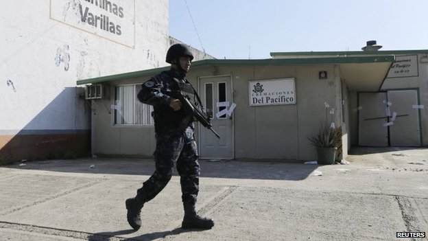 A police officer walks outside the sealed-off building housing a crematorium in Llano Largo, on the outskirts of Acapulco, Mexico.