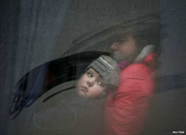 A woman and a child look through a bus window before leaving as people flee the conflict in Debaltseve, eastern Ukraine, 6 February