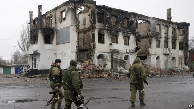 Pro-Russian rebels walk past a destroyed building in the town of Vuhlehirsk, Ukraine, 6 February 2015