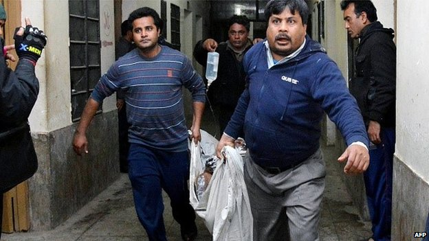 Rescuers carry a man with burn injuries after the petrol bomb attack on a bus from Gaibandha to Dhaka, 7 February 2015