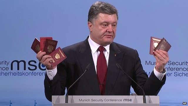 Ukraine's president Petro Poroshenko holding up six Russian passports at a conference to discuss ways to end the Ukraine conflict