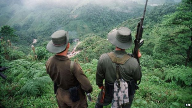 Two armed soldiers belonging to the Revolutionary Armed Forces of Colombia (FARC) monitor the Berlin pass, 07 March, near Florencia, in the southern Caqueta province of Colombia