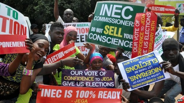 People hold signs to protest against the postponement of elections, in Abuja, Nigeria, 7 February 2015