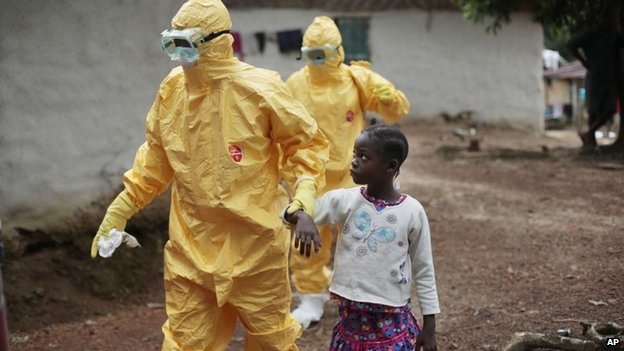 Young girl is taken to an ambulance by men in protection suits after showing signs of Ebola