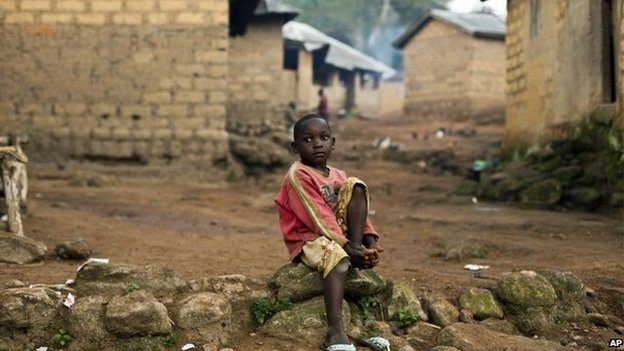 a child sits in the Guinean village of Meliandou