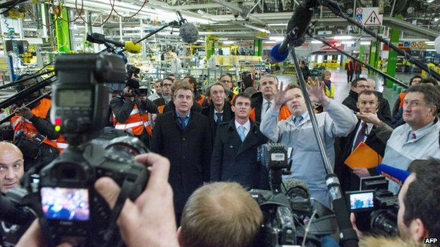 Members of the media surround French Prime Minister Manuel Valls (C) and Socialist Party (PS) parliamentary candidate Frederic Barbier (C-L) as they visit the French carmaker PSA Peugeot plant in Montbelliard, eastern France, on February 5, 2015