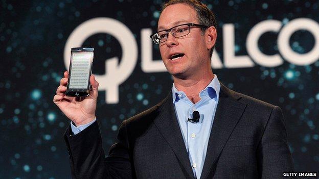 Qualcomm president Derek Aberle displays a LG G Flex 2 smartphone that contains Qualcomm's Snapdragon 810 chip