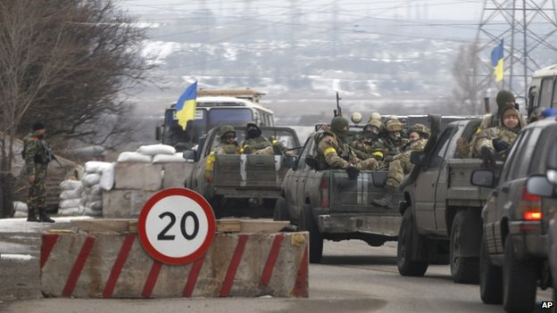 Ukrainian government troops sit in the back of pick-up trucks as they pass a checkpoint near the town of Mariupol, Ukraine, Tuesday 10 February 2015