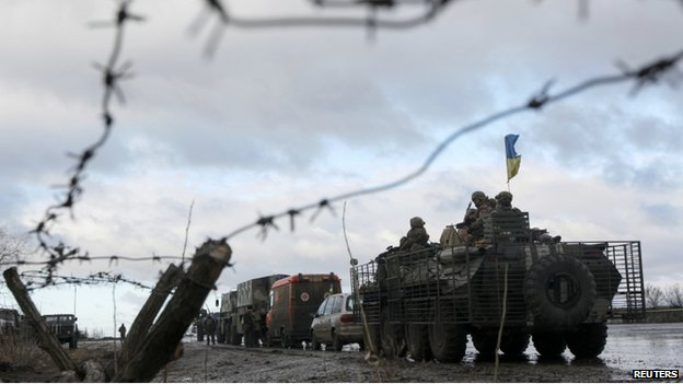 Ukrainian military convoy is pictured through a barbed wire fence at a military base in the town of Kramatorsk, eastern Ukraine, 24 December 2014