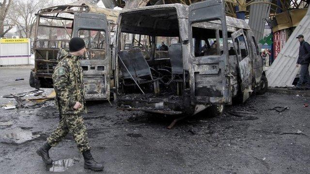 Pro-Russian rebels walk past damaged buses at a bus station in Donetsk, Ukraine,