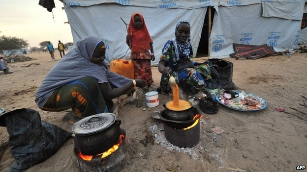 Nigerian refugee women cook in a United Nations Refugee Agency (UNHCR) refugee camp in Baga Sola by Lake Chad, which borders Chad, Nigeria, Niger and Cameroon, on 26 January 2015