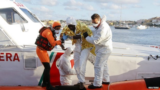 A migrant is helped as he arrives with others at the Lampedusa harbour - 11 February 2015