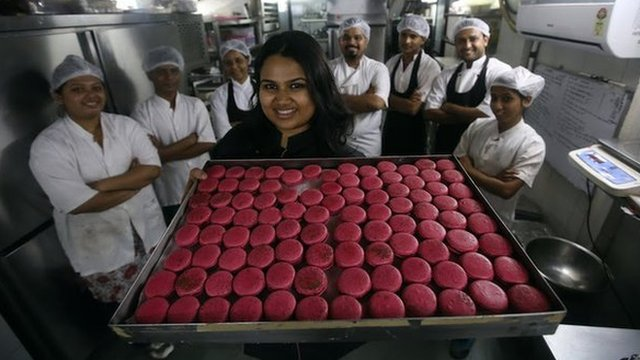 Pooja Dhingra holding a tray of macaroons in front of some members of staff