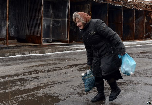 A woman passes a charred market in Donetsk city, 11 February