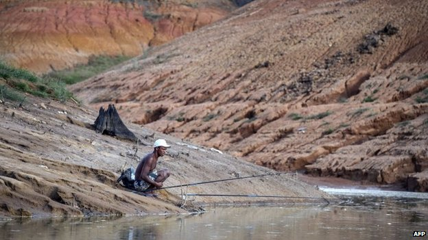 A man tries to fish on a bank dried due to the lack of rain at Funil Hydroelectric Plant reservoir on 3 February, 2015.