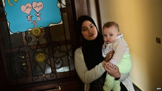 Jihan Rashid, the wife of Al Jazeera English producer Baher Mohamed, with one of their children (8 February 2015)