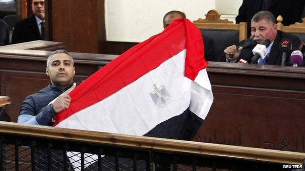 Mohamed Fahmy unfurls an Egyptian flag after addressing a court in Cairo on 12 February 2015