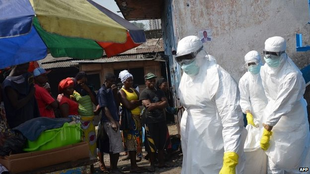Red cross workers, wearing protective suits, carry the body of a person who died from Ebola during a burial with relatives of the victims of the virus, in Monrovia, on January 5, 2015