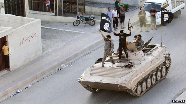 Militant Islamist fighters hold aloft the flag of Islamic State (IS) while taking part in a military parade along the streets of northern Raqqa province