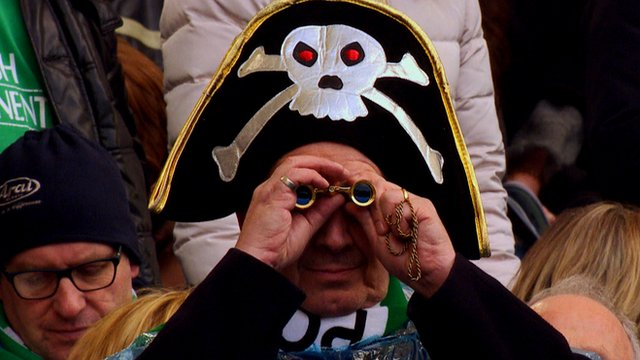 A fan in a pirate hat watches the rugby through binoculars