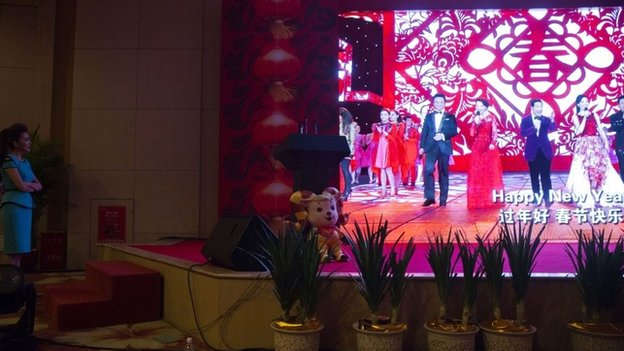 A moderator, left, looks on as a video showing previous galas is displayed at a press conference ahead of the China Central Television's annual hours-long Spring Festival Gala held in Beijing, Monday, Feb. 2, 2015.