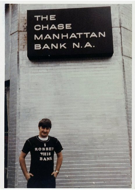 Wojtowicz poses in a T-shirt that says 'I robbed this bank' - in front of the bank