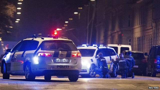 Police personnel and vehicles are seen along a street in central Copenhagen following shootings at a synagogue in Krystalgade