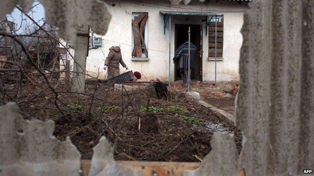 Residents clear up debris in the village of Opytne, near Artemivsk in the Donetsk region