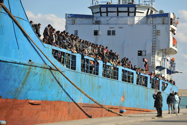 """Immigrants part of a group of more than 580 people, most of them from Syria, disembark from the Congolese cargo """"Sandy"""" after a rescue operation by the Guardia Costiera as part of the Frontex joint operation """"Triton"""" on December 9, 2014 in the port of Crotone, southern Italy."""