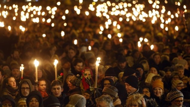 People gather during a vigil in honour of the two men killed by a gunman over the weekend