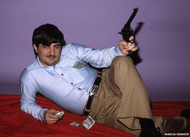 John Wojtowicz poses with gun and money