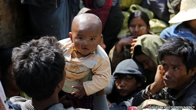 A man takes care of his baby onboard rescue truck fleeing from Kokang capital Laukkai, on 17 February 2015