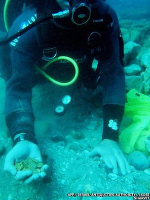A scuba diver holding in his hand some of the gold coins recently found on the seabed at the Israeli town of Caesarea